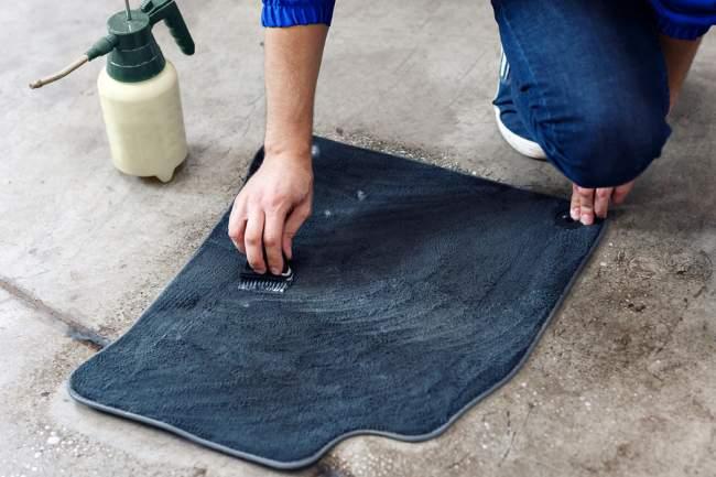 applying shampoo to car carpet
