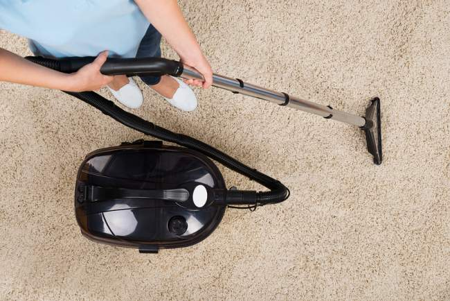 using a vacuum attachment to clean shag rug